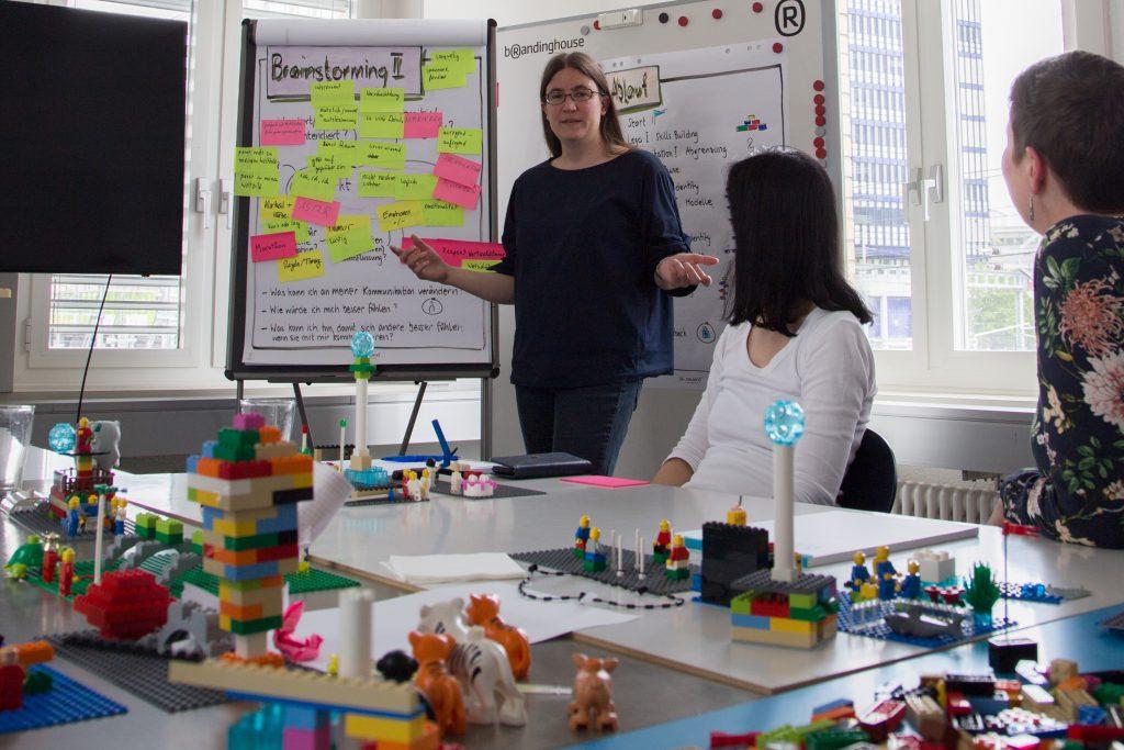 Die Trainerin Sascha vor einer Gruppe von Teilnehmenden, im Hintergrund Flipcharts, teilweise mit Klebezetteln versehen, im Vordergrund Tische mit Legos, Papier und Stiften.